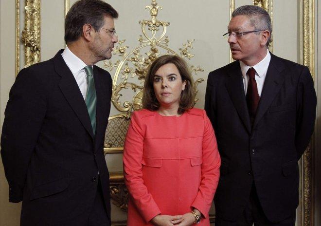 Rafael Catalá (iqda) conversa con su antecesor en el cargo, Alberto Ruiz-Gallardón, en presencia de la vicepresidenta del Gobierno, Soraya Sáenz de Santamaría, que acudió a la  ceremonia de traspaso de poderes en el Ministerio de Justicia.